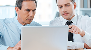 Two businessmen looking at laptop screen
